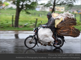 Man with his load of scraps on a moped during a rainy day
